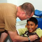 A doctor examining a child with cerebral palsy